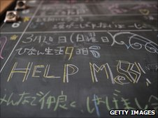 A school board in an English class room reads ''help me'' at a relief centre in the tsunami-damaged city of Rikuzentakata