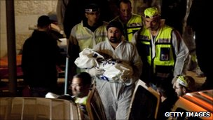 An rescue worker carries away the body of Hadas Fogel in the Jewish West Bank settlement of Itamar, 12 March
