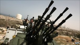 A Libyan rebel guards oil facilities near the rebel-held port town of Brega (29 March 2011)