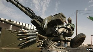A Libyan rebel sits at an anti aircraft gun in the strategic oil town of Ajdabiya