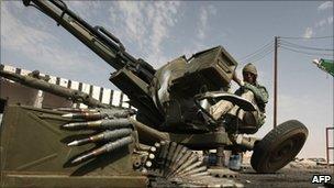 A Libyan rebel sits at an anti aircraft gun in the strategic oil town of Ajdabiya