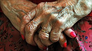 An elderly lady holds her hands on her lap