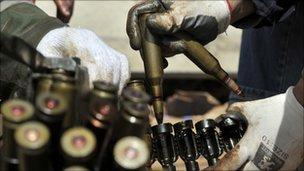 Libyan rebels prepare an ammunition belt near Nufilia (29 March 2011)