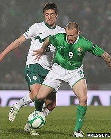 Armin Bacinovic of Slovenia closes in as Northern Ireland's Warren Feeney shields the ball
