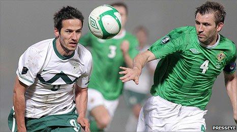Slovenia's Zlatan Ljubijankic battles for the ball with Northern Ireland captain Gareth McAuley