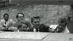 President Reagan is pushed into his waiting limousine by Secret Service agents after being shot