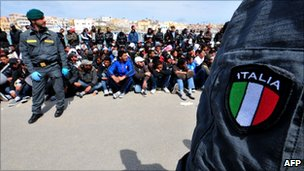 An Italian policeman watches over migrants on the island of Lampedusa (29 March 2011)