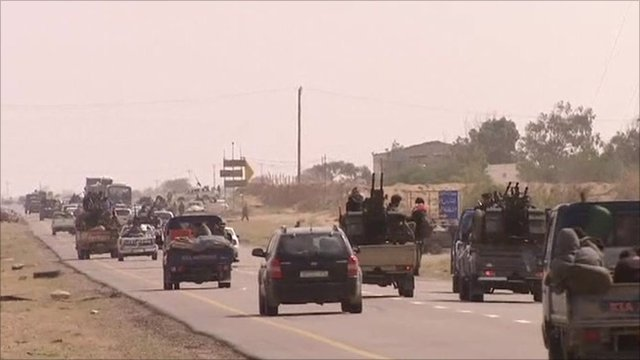 Rebel forces travelling along a road in cars and trucks