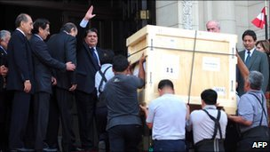 Peruvian President Alan Garcia waves to the press as workers carry a crate of Inca artefacts into a government office in Lima