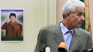 Libyan Foreign Minister Moussa Koussa speaking in Tripoli with a portrait of Muammar Gaddafi in the background, 18 March