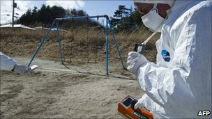 A Greenpeace member holds up a Geiger counter to monitor radioactivity levels at Iitate village, Japan, 27 March