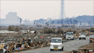 Small trucks drive down a road with the Fukushima Daiichi plant in the background