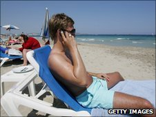 An english tourist uses his mobile phone on a beach in Ibiza, Spain (file photo)