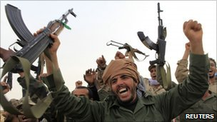 Libyan government soldiers celebrate at the west gate of town Ajdabiya, March 16, 2011
