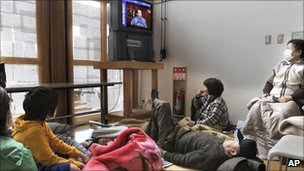 People in a temporary shelter in Fukushima prefecture watch Prime Minister Naoto Kan give an address on 15 March 2011
