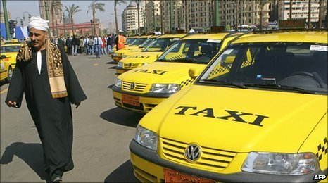 A man walks past a taxi rank in Cairo