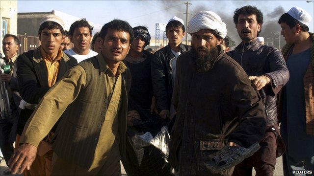 Afghan men carrying one of the injured