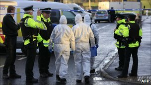 Forensic officers walk from the scene of a bomb that killed a Northern Ireland Police Officer