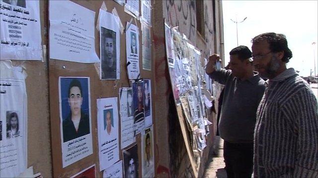 Two men read a notice-board outside Benghazi's media centre