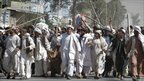 Afghan protesters walk with sticks, as they carry a wounded colleague during a demonstration to condemn the burning of a copy of the Koran a US Florida pastor, in Kandahar, 2 April 2011.
