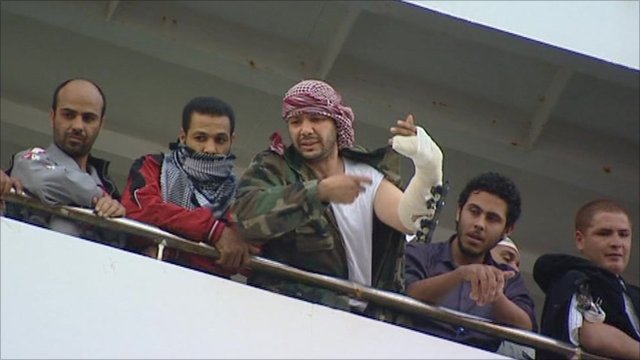 A group of men, one with a bandaged arm, arrive on a ship arriving in Benghazi