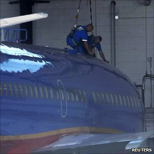 Mechanics work on a Southwest Airlines Boeing 737 at the Phoenix Sky Harbor International Airport in Phoenix, Arizona (2 April 2011)