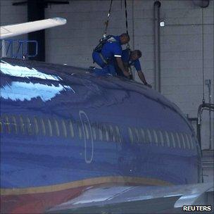 Mechanics work on a Southwest Airlines Boeing 737 at the Phoenix Sky Harbor International Airport in Phoenix, Arizona (2 April 2011)