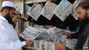 Pakistani men reading Urdu newspapers