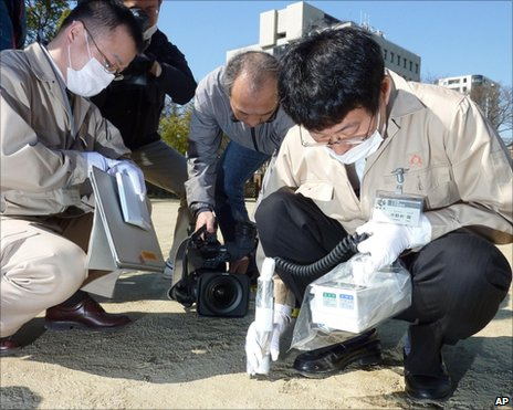 Officials monitor radiation on the ground of an elementary school in Fukushima, Japan, 5 April