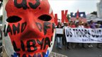 An activist wears a mask decorated with slogans during a march to the US embassy in Manila to coincide with start of a Philippines-US annual military exercise