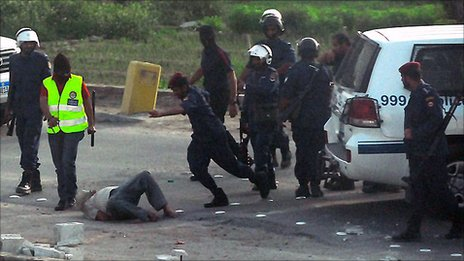 A policeman kicks a bound man in Manama, 30 March (obtained from a human rights group)