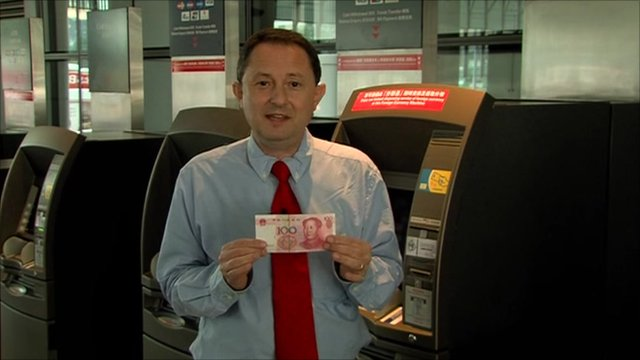 The BBC's Andrew wood holding up a 100 renminbi note.