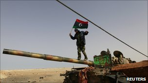 A Libyan rebel fighter walks on a tank near Brega, 6 April 2011.