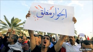 Protestor holds a sign in Pearl Roundabout