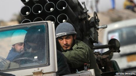 Libyan rebels ride in a vehicle with a rocket launcher on the road to Brega, 6 April