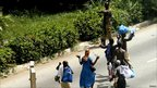 Residents pass pro-Gbagbo soldiers. 3 April 2011