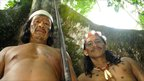 Two Huaorani men display a blowpipe against a tall tree
