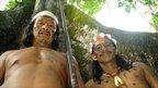 Two Huaorani men display a blowpipe against a tall tree