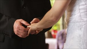 Man places wedding ring on bride's finger