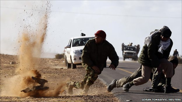 Rebel fighters jump away from shrapnel during heavy shelling, 6 March 2011