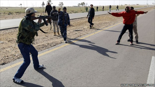 A rebel fighter points his gun at a suspected Gaddafi supporter, 21 March 2011