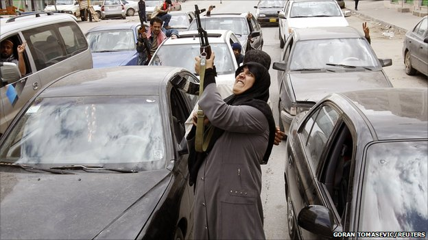 A woman rebel fighter supporter shoots an AK-47 rifle as she reacts to the news of the withdrawal of Libyan leader Colonel Gaddafi's forces from Benghazi, 19 March