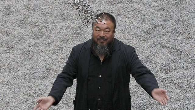 Designer Ai Weiwei standing in his sunflower seeds installation at the Tate Modern