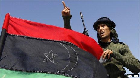 A rebel fighter gestures beside a Kingdom of Libya flag