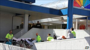Injured people are carried out of a shopping mall after a shooting in Alphen aan den Rijn, 15 miles (25km) southwest of Amsterdam, Netherlands, 9 April 2011