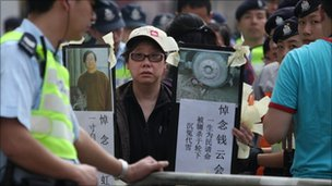 A woman holds banners denouncing China&#039;s government and the detention of mainland dissidents, during a protest outside the Chinese liaison office in Hong Kong on April 3, 2011