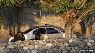 Police stand near a car with the bodies of seven dead people in Cuernavaca