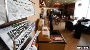 Newspapers with headlines reporting Bahrain has suspended opposition newspaper Al-Wasat in a coffee shop in Manama, 3 April