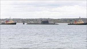 HMS Astute leaving Southampton between two tugs