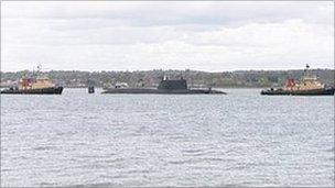 HMS Astute leaving Southampton between two tugs